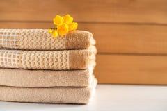 Stapel beige handdoeken op houten achtergrond stock foto