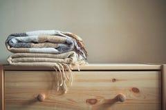 Stapel beige karierte Wolldecken auf einem hölzernen Kasten stockfotos