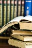 Stapel benutzte alte geöffnete Bücher, Volumen mit beeindruckter Abdeckung im Hintergrund, Hochschulbildung, Konzept lesend Stockfoto