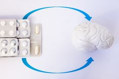 Stapel blaren met capsule of pil door pijlen in anatomisch model van menselijke hersenen wordt vermeld die De behandeling van de  royalty-vrije stock foto's