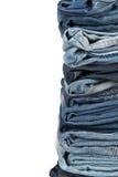 Stapel Blue Jeans über einem weißen Hintergrund Lizenzfreie Stockfotografie