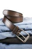 Stapel Blue Jeans mit braunen Gurten stockbilder