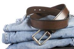 Stapel Blue Jeans mit braunen Gurten stockfoto