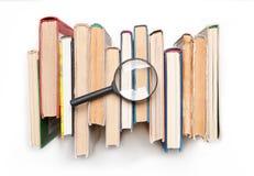 Stapel boek met harde kaftboeken met vergrootglas op witte achtergrond, hoogste mening wordt geïsoleerd die Zoek naar relevante e Royalty-vrije Stock Afbeelding