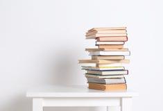 Stapel boek met harde kaftboeken op de witte lijst Zoek naar relevante en noodzakelijke informatie Royalty-vrije Stock Foto's