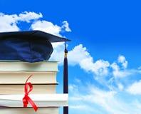 Stapel boeken met diploma tegen blauwe hemel Stock Afbeeldingen