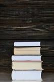 Stapel boeken met donkere houten achtergrond Verticale orientatio Stock Foto's