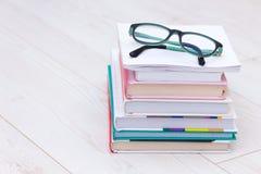 Stapel boeken met glazen op bovenkant Conceptenoorzaak van verziendheid, bijziendheid stock fotografie