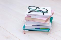 Stapel boeken met glazen op bovenkant Conceptenoorzaak van verziendheid, bijziendheid royalty-vrije stock afbeeldingen