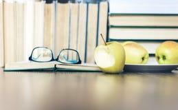 Stapel boeken, open boek, glazen en groene appelen, achtergrond voor onderwijs het leren concept royalty-vrije stock afbeelding