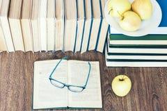 Stapel boeken, open boek, glazen en groene appelen, achtergrond voor onderwijs het leren concept stock afbeelding