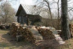 Stapel Brennholz nahe verfielen Blockhaus im russischen Dorf Stockbilder