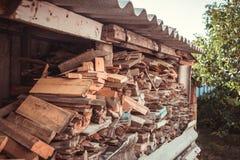 Stapel Brennholz unter dem Dach nahe dem Haus lizenzfreie stockbilder