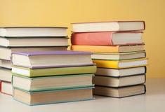 Stapel bunte Bücher auf dem Holztisch Scheren und Bleistifte auf dem Hintergrund des Kraftpapiers Zurück zu Schule Lizenzfreies Stockfoto