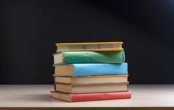 Stapel bunte Bücher auf dem Holztisch Scheren und Bleistifte auf dem Hintergrund des Kraftpapiers Zurück zu Schule Stockfotografie