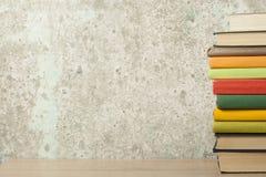 Stapel bunte Bücher auf dem Holztisch Scheren und Bleistifte auf dem Hintergrund des Kraftpapiers Zurück zu Schule Kopieren Sie R Stockfotografie