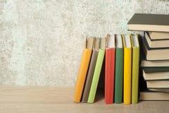 Stapel bunte Bücher auf dem Holztisch Scheren und Bleistifte auf dem Hintergrund des Kraftpapiers Zurück zu Schule Kopieren Sie R Stockfotos