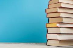 Stapel bunte Bücher auf dem Holztisch Scheren und Bleistifte auf dem Hintergrund des Kraftpapiers Zurück zu Schule Kopieren Sie R Lizenzfreie Stockbilder