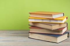 Stapel bunte Bücher auf hölzernem Schreibtisch, Freiexemplarraum Zurück zu Schule Scheren und Bleistifte auf dem Hintergrund des  Lizenzfreies Stockbild