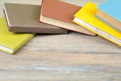 Stapel bunte Bücher auf hölzernem Schreibtisch, Freiexemplarraum Zurück zu Schule Scheren und Bleistifte auf dem Hintergrund des  Stockfotos