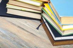 Stapel bunte Bücher auf hölzernem Schreibtisch, Freiexemplarraum Zurück zu Schule Scheren und Bleistifte auf dem Hintergrund des  Stockbilder