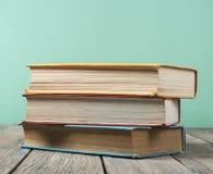 Stapel bunte Bücher auf hölzernem Schreibtisch, Freiexemplarraum Zurück zu Schule Scheren und Bleistifte auf dem Hintergrund des  Stockfoto