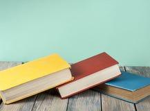 Stapel bunte Bücher auf hölzernem Schreibtisch, Freiexemplarraum Zurück zu Schule Scheren und Bleistifte auf dem Hintergrund des  Lizenzfreie Stockfotos