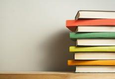 Stapel bunte Bücher auf hölzernem Schreibtisch Kopieren Sie Raum für Text Zurück zu Schule Scheren und Bleistifte auf dem Hinterg Stockfotografie