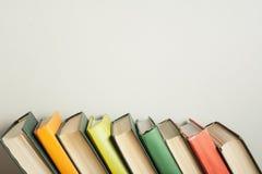 Stapel bunte Bücher auf hölzernem Schreibtisch Kopieren Sie Raum für Text Zurück zu Schule Scheren und Bleistifte auf dem Hinterg Stockfoto