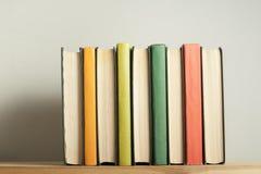 Stapel bunte Bücher auf hölzernem Schreibtisch Kopieren Sie Raum für Text Zurück zu Schule Scheren und Bleistifte auf dem Hinterg Lizenzfreies Stockbild