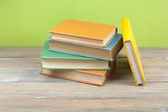 Stapel bunte Bücher auf hölzernem Schreibtisch Kopieren Sie Raum für Text Zurück zu Schule Scheren und Bleistifte auf dem Hinterg Stockbild
