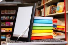 Stapel bunte Bücher mit Ebuch Leser lizenzfreie stockfotos