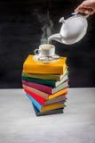 Stapel bunte Bücher mit einer Tasse Tee auf ihr und Teekanne lizenzfreie stockbilder