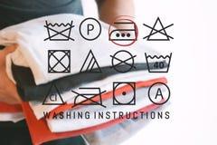 Stapel bunte gefaltete Hemden mit Wäschereianweisungssymbol stockbild