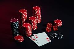 Stapel Chips und zwei Karten auf dunklem Hintergrund - Pokerspielkonzept Lizenzfreie Stockbilder