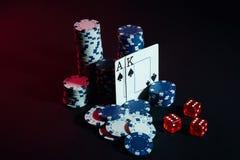 Stapel Chips und zwei Karten auf dunklem Hintergrund - Pokerspielkonzept Stockfotos