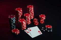 Stapel Chips und zwei Karten auf dunklem Hintergrund - Pokerspielkonzept Lizenzfreie Stockfotos