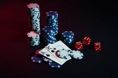Stapel Chips und zwei Karten auf dunklem Hintergrund - Pokerspielkonzept Lizenzfreie Stockfotografie
