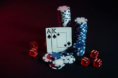 Stapel Chips und zwei Karten auf dunklem Hintergrund - Pokerspielkonzept Stockfoto