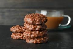 Stapel chocoladekoekjes en kop van koffie op zwarte lijst stock foto's