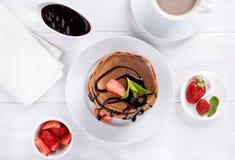 Stapel chocoladepannekoeken met chocoladebovenste laagje en aardbeien Hoogste mening royalty-vrije stock fotografie