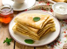 Stapel dünne Pfannkuchen kräuselt bliny gedient mit Honig Stockfotos