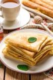 Stapel dünne Pfannkuchen kräuselt bliny gedient mit Honig Lizenzfreies Stockfoto