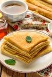 Stapel dünne Pfannkuchen kräuselt bliny gedient mit Honig Lizenzfreie Stockbilder