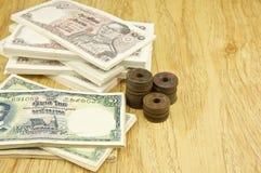 Stapel der alten alten Rechnung und Münzen von Thailand Stockbild