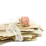 Stapel der alten Liebesbriefe, der Spitzes und der rosafarbenen Blume Stockfotografie