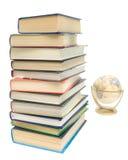Stapel der Bücher und der Kugel auf einem weißen Hintergrund Lizenzfreie Stockfotos
