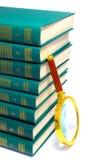Stapel der Bücher und des Vergrößerungsglases Lizenzfreie Stockfotografie