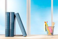 Stapel der Buch-Stellung und -bleistifte im Korbbehälter mit grünem Hefter auf dem Holztisch stockbild
