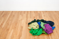 Stapel der bunten Kleidung auf dem hölzernen Fußboden Lizenzfreie Stockbilder
